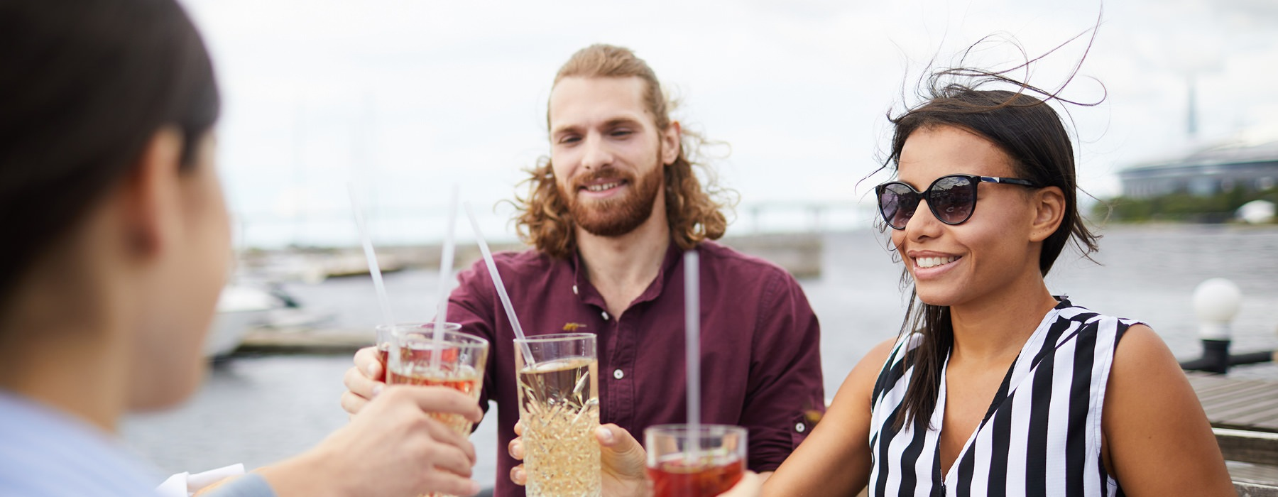young friends on a balcony overlooking the pier, toasting drinks around a table of food