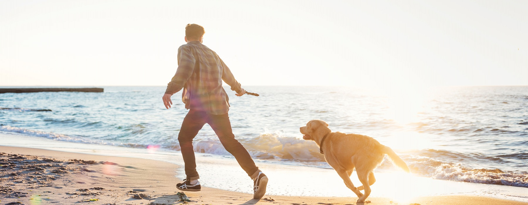 man holding a stick behind him as dog chases him down the beach